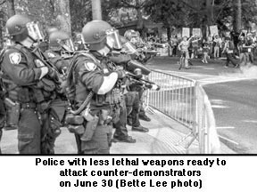 June 30 photo of police with less lethal weapons ready to  attack  counter-demonstrators. Photo by Bette Lee.